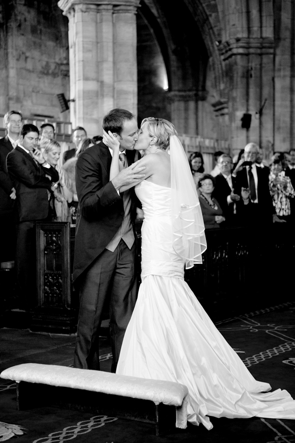 Bride and groom kissing at wedding ceremony at St. Michaels' Parish in Linlithgow