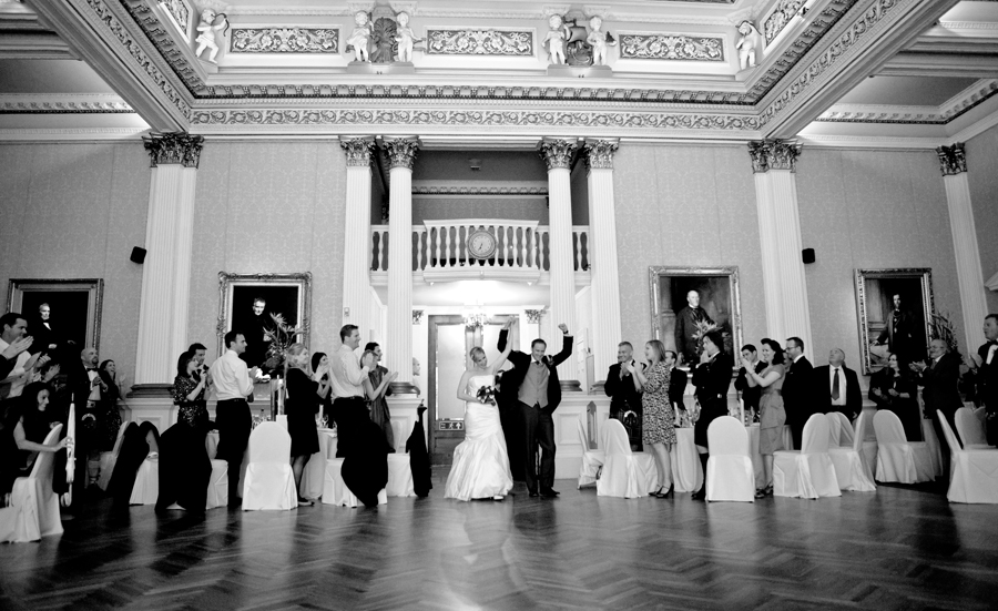 Happy bride and groom entering Merchant's Hall in Edinburgh