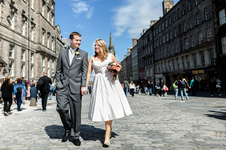 Happy bride and groom walking on Royal Mile