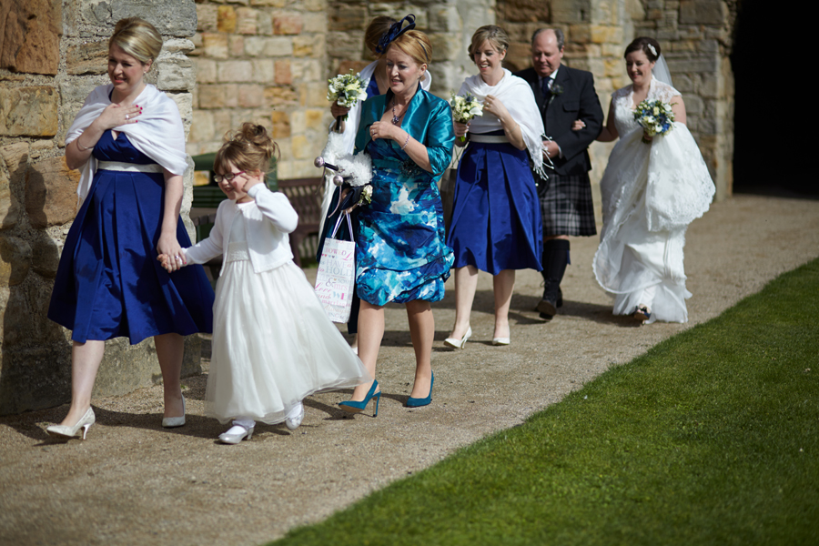 Bride, her father and her bridesmaids marching to Inchcolm Abbey for the wedding ceremony