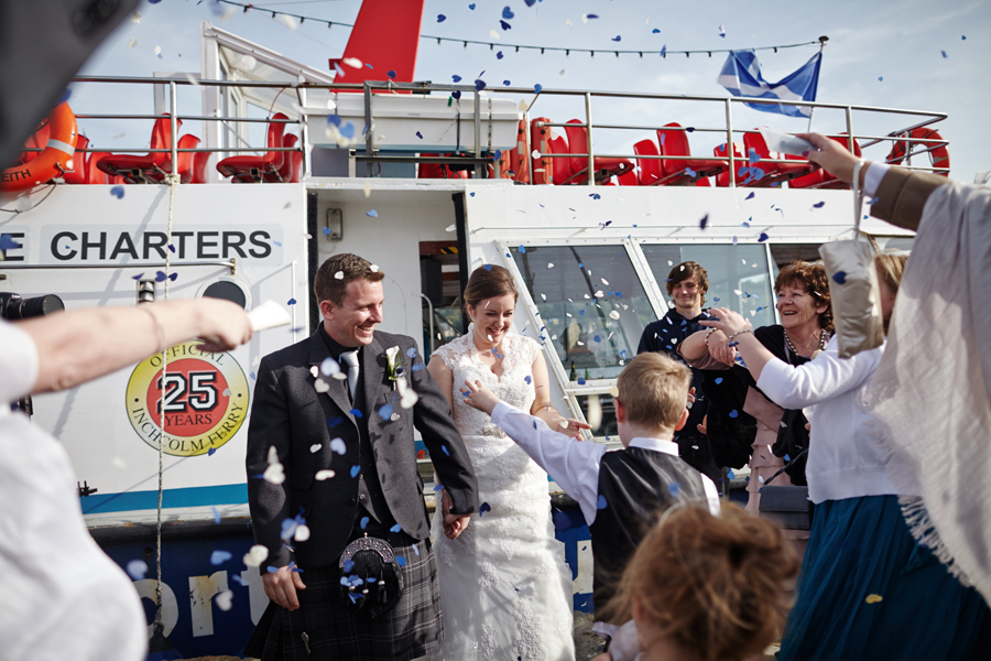 Bride and groom and their guests throwing confetti at Orocco Pier in Southqueensferry