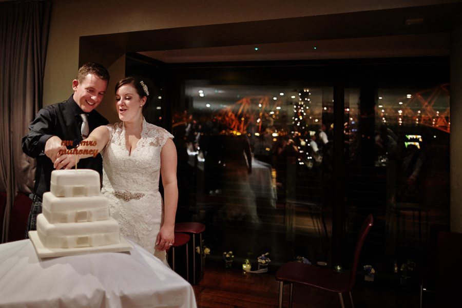Bride and groom cutting the cake at Orocco Pier in South Queensferry during their wedding