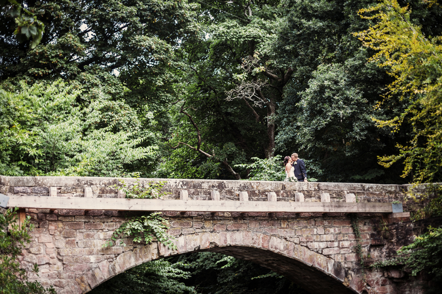 Bride and groom kissing on the bridge at Dalhousie Castle in Bonnyrig