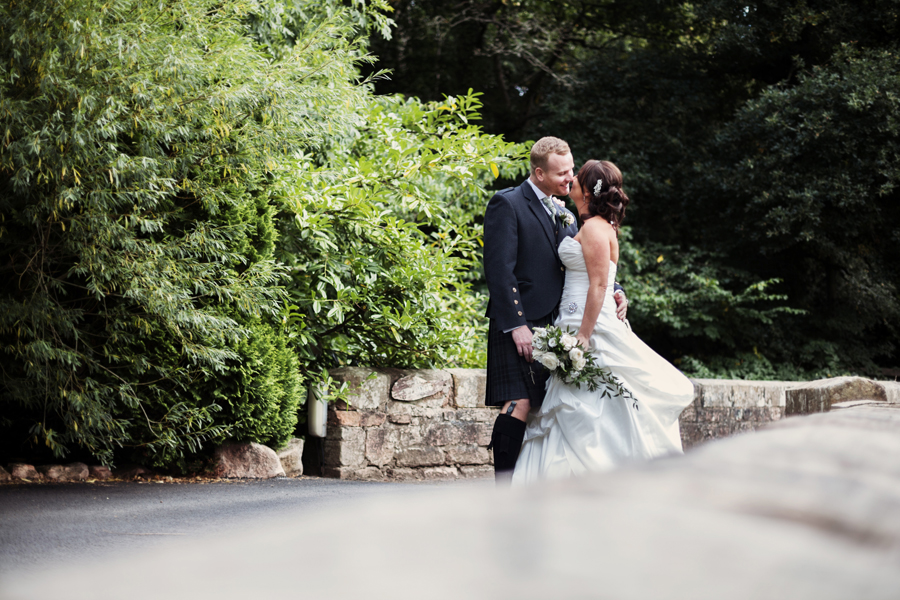 Bride and groom kissing on the bridge on the grounds of Dalhousie Castle