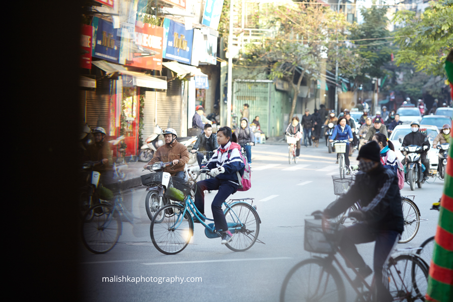 Early morning cyclists on the streets of Hanoi