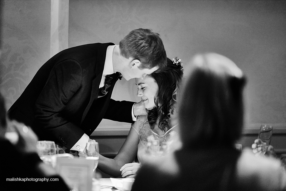 Tender moment between bride and groom during the speeches