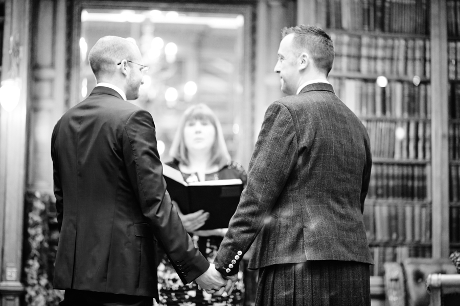 Partners holding hands during civil partnership at Royal College of Physicians in Edinburgh