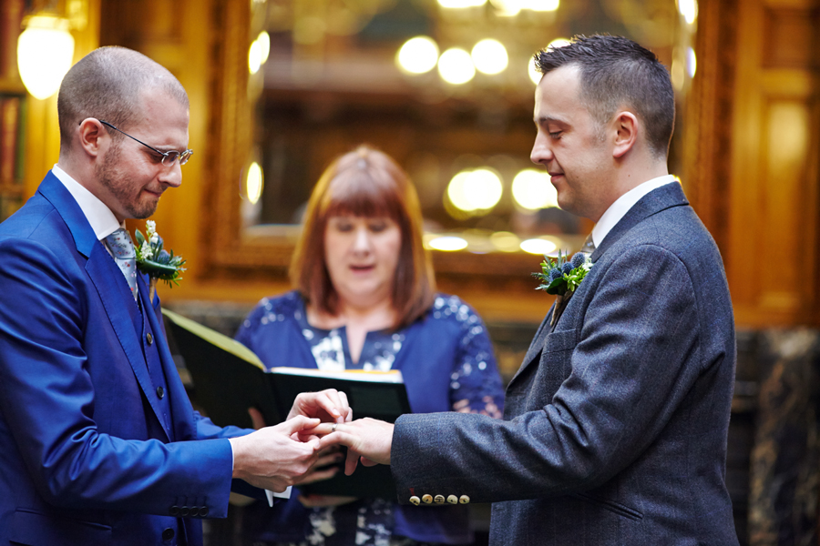Partners exchanging rings during civil partnership ceremony at Royal College of Physicians in Edinburgh