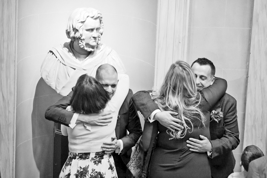 Guests hugging the grooms at civil partnership at Royal College of Physicians in Edinburgh