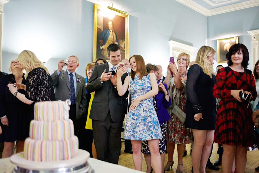 Guests photographing the cake during the wedding ceremony at Royal College of Physicians in Edinburgh